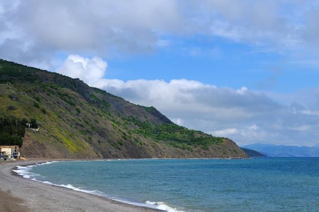 Riva di mare e spiaggia rocciosa, cielo nuvoloso blu