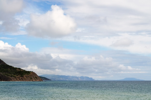Riva del mare e spiaggia rocciosa, cielo azzurro con nuvole bianche, montagne e piccolo villaggio a