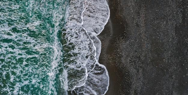Riva del mare con una trama drammatica di onde che si infrangono e sabbia nera, prospettiva drone