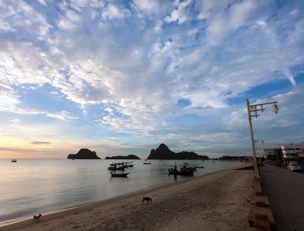 Mare nella stagione estiva durante l'alba del mattino con piccola barca e cielo nuvoloso.