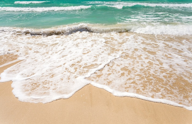 Navigare in mare su una spiaggia sabbiosa, mare, onde e schiuma nell'acqua