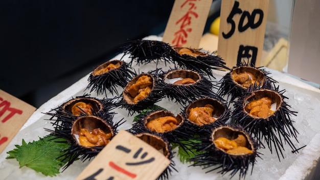 Sashimi di ricci di mare aperto fresco e pronto da mangiare su ghiaccio nel mercato del pesce di kyoto. primo piano di deliziosi frutti di mare tradizionali giapponesi uni in stallo per la vendita. spuntino di strada del negozio di viaggi e cucina in giappone