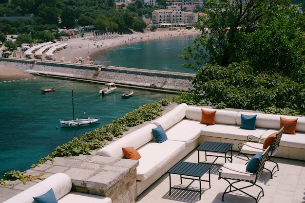 Ristorante vista mare comodi divani con cuscini e sedie in ferro battuto vicino all'acqua