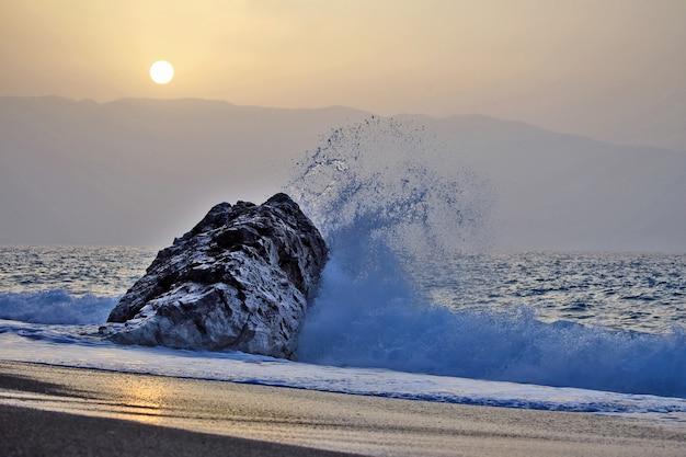 L'onda del mare batte sulla roccia contro il tramonto