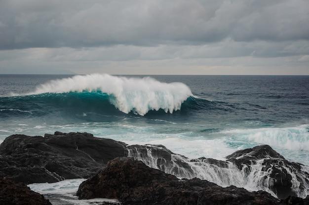 Onda del mare con schiuma e roccia nera sotto il cielo grigio nuvoloso il giorno tempestoso