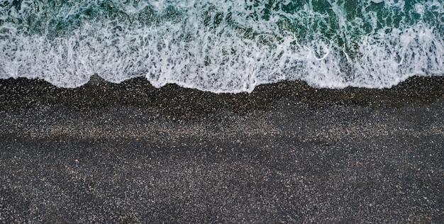 Onde del mare che si infrangono sulla spiaggia di sabbia nera, sfondo marino aereo