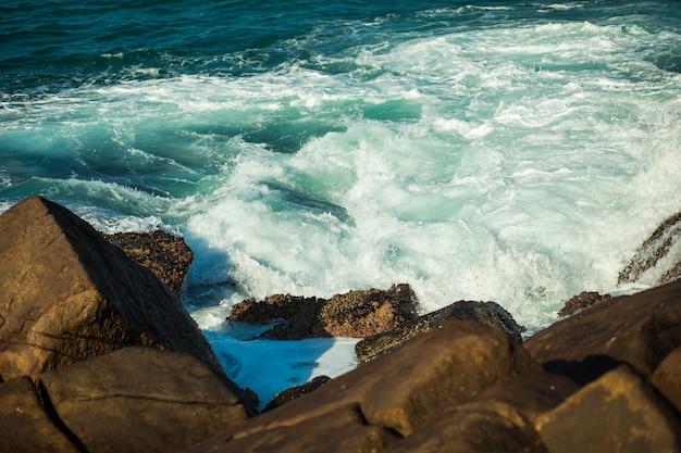 Onde del mare che si infrangono sullo sfondo di rocce