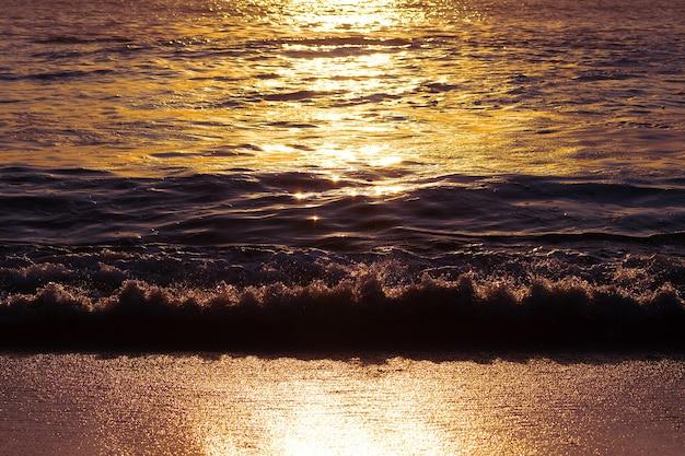 Onde del mare e sabbia dorata al tramonto. riflesso del sole sull'acqua