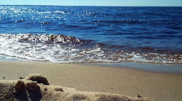 Le onde del mare lavano la spiaggia sabbiosa