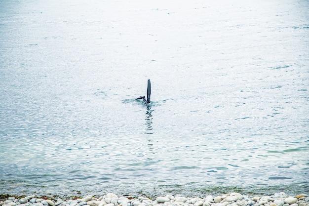 Il mare si vedono le onde e in primo piano le pinne di un palombaro
