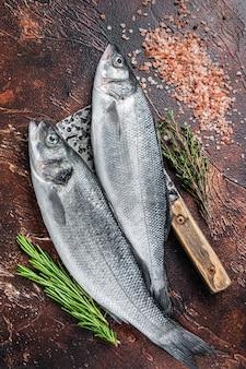 Branzino o branzino pesce crudo fresco su una mannaia con sale ed erbe aromatiche. sfondo scuro. vista dall'alto.