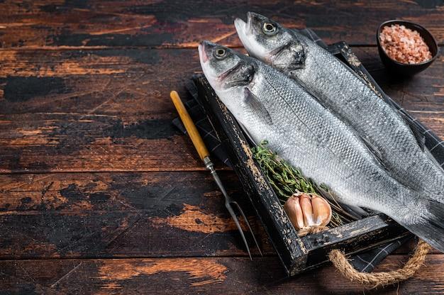 Pesce crudo di branzino o branzino in un vassoio di legno con erbe aromatiche. fondo in legno scuro. vista dall'alto. copia spazio.