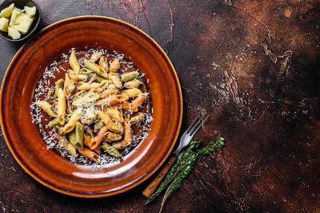 Colore dei frutti di mare penne in salsa di panna su un piatto. sfondo scuro. vista dall'alto. copia spazio.