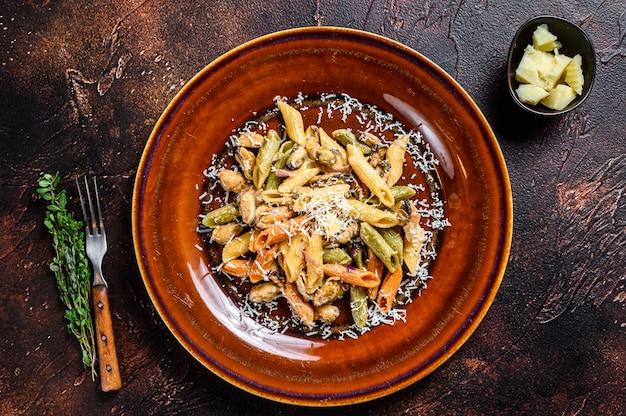 Colore dei frutti di mare penne in salsa di panna su un piatto. sfondo scuro. vista dall'alto.