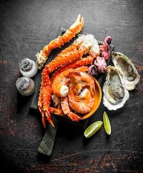 Frutti di mare. granchio, gamberetti, ostriche, moscardini su un tagliere con spezie e fettine di lime sul tavolo rustico nero