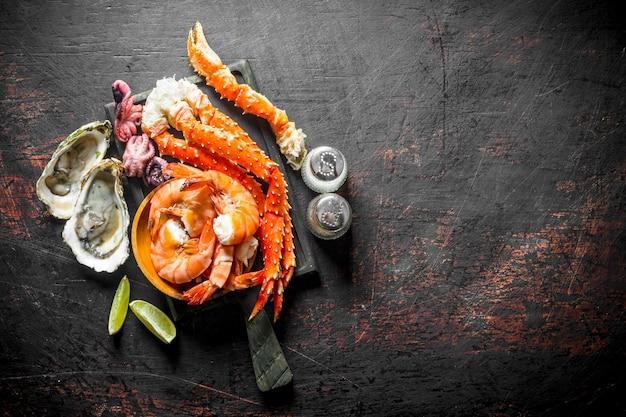 Frutti di mare. granchio, gamberi, ostriche, moscardini su un tagliere con spezie e fettine di lime.