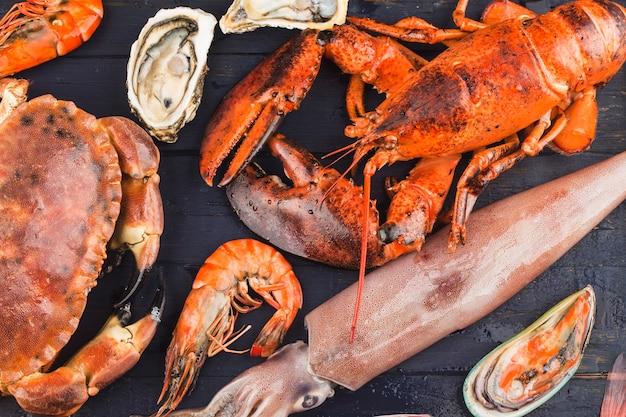Cena a base di pesce, cena a base di pesce con aragosta fresca, granchio, cozze e ostriche come sfondo Foto Premium