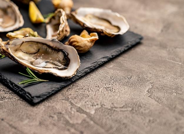 Set di lusso di frutti di mare di ostriche fresche e lumache cotte sul piatto nero