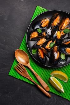 Cozze di frutti di mare e foglie di basilico in un piatto nero su stuoia di bambù e tavolo in pietra. vista dall'alto.