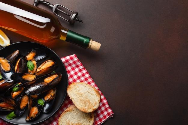 Cozze di frutti di mare e foglie di basilico in un piatto nero con bottiglia di vino e cavatappi su asciugamano e sfondo arrugginito. vista dall'alto con posto per il testo.