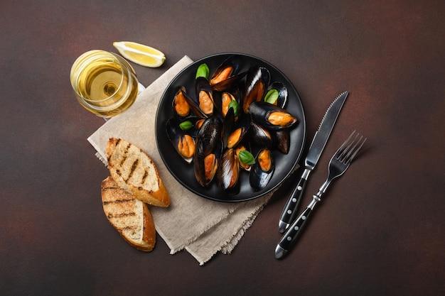 Cozze di frutti di mare e foglie di basilico in un piatto nero con bicchiere di vino, fette di pane, forchetta, coltello, tela su sfondo arrugginito. vista dall'alto.