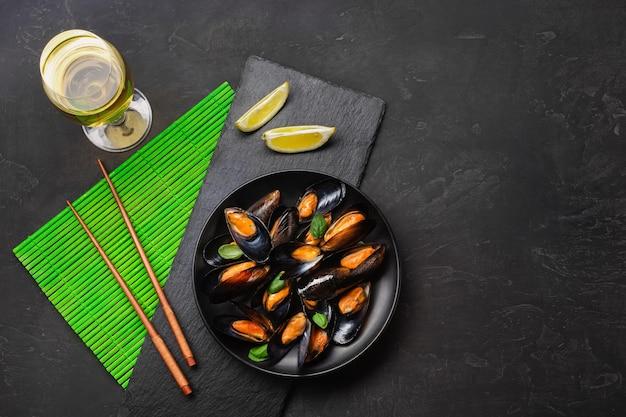 Cozze di frutti di mare, foglie di basilico in un piatto nero con bicchiere di vino, limone e bacchette su stuoia di bambù verde e tavolo in pietra. vista dall'alto.