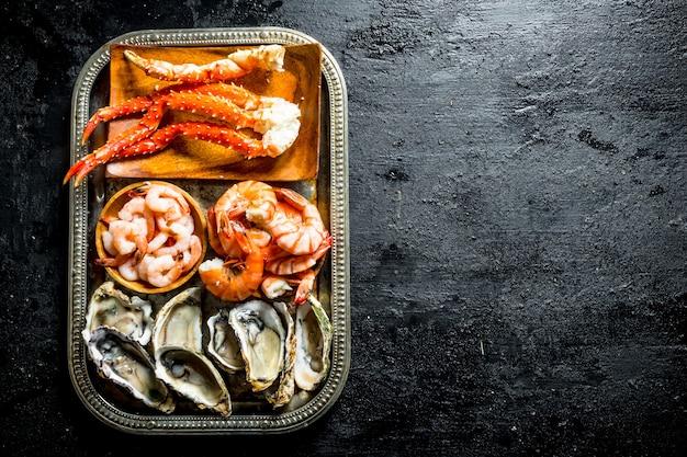 Frutti di mare. ostriche, gamberi e granchi sul vassoio.