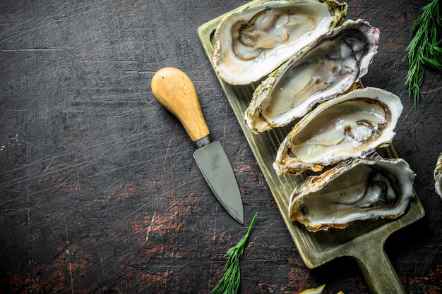 Frutti di mare. ostriche aperte crude sul tagliere con coltello sul tavolo di legno scuro