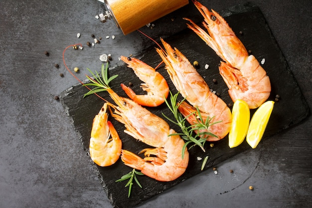 Gamberi crudi di frutti di mare con spezie e limone su una tavola di ardesia vista dall'alto fondo piatto disteso