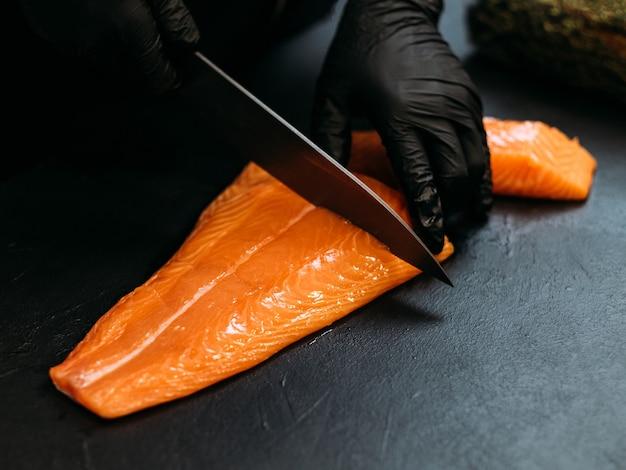 Ristorante di pesce. primo piano delle mani dello chef usando il coltello per tagliare il filetto di salmone fresco.