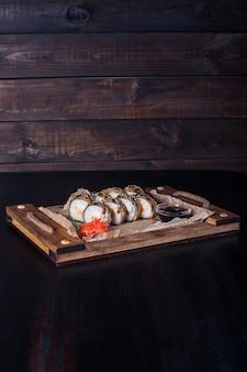 Frutti di mare rotoli su un vassoio di legno, bella porzione, sfondo scuro.