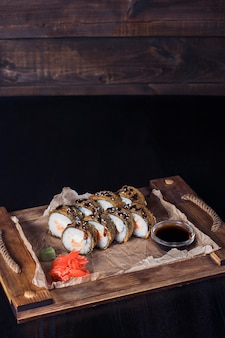 Frutti di mare rotoli su un vassoio di legno, bella porzione, superficie scura.