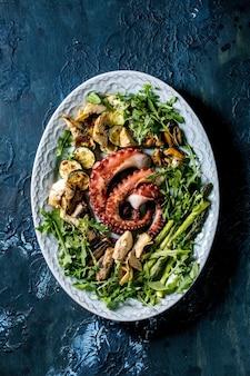 Insalata di mare. tentacoli cotti alla griglia di polpo, sardine e cozze su piatto in ceramica blu servito con insalata di rucola, zucchine e asparagi su superficie blu. vista dall'alto, posizione piatta