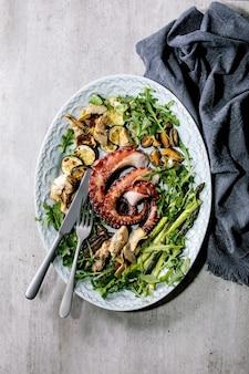 Insalata di mare. tentacoli cotti alla griglia di polpo, sardine e cozze su piatto in ceramica blu servito con insalata di rucola, zucchine e asparagi su superficie grigia. vista dall'alto, piatto. copia spazio