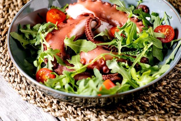 Insalata di mare. tentacoli di polpo cotti su piatto in ceramica blu serviti con rucola e insalata di pomodorini su superficie in legno grigio e rivestimento in vimini.