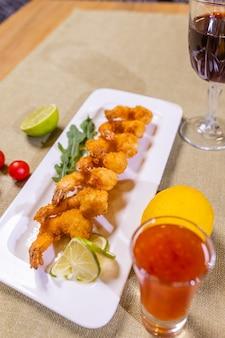 Frutti di mare crostacei fritto gamberi alla griglia gamberi su spiedini di legno bicchiere di vino bianco snack antipasto ...