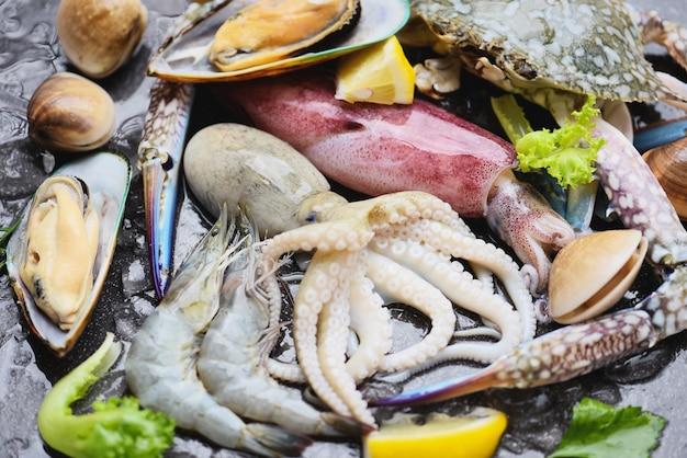 Frutti di mare crostacei su ghiaccio congelati con gamberi gamberi chele di granchio conchiglia vongole veraci calamari polpi e cozze al ristorante, buffet di pesce crudo fresco con limone rosmarino ingredienti erbe e spezie