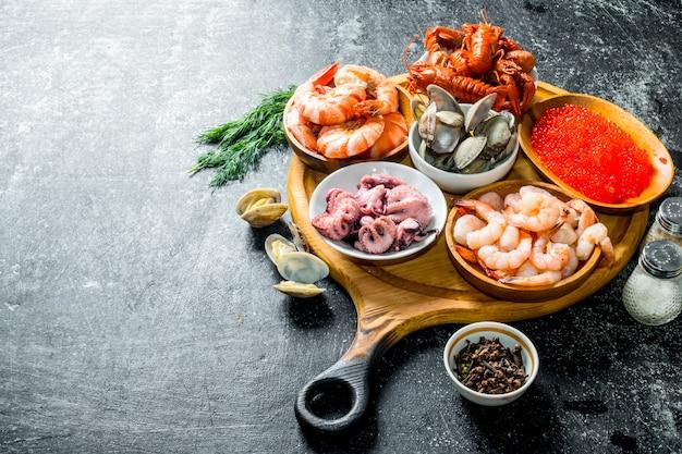 Frutti di mare. gamberi, gamberi, ostriche, polpi e caviale in ciotole sul tagliere.