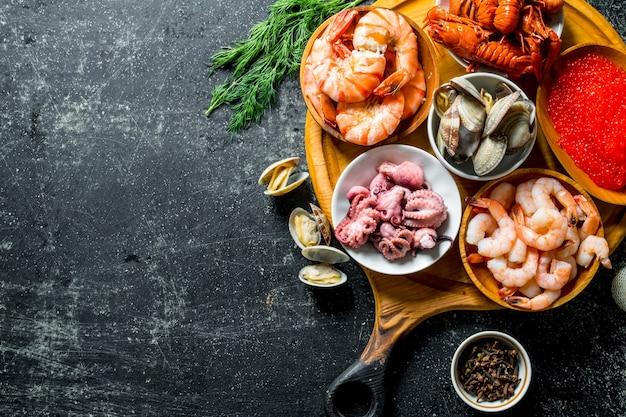 Frutti di mare. gamberetti, gamberi, ostriche, polpi e caviale in ciotole sul tagliere.