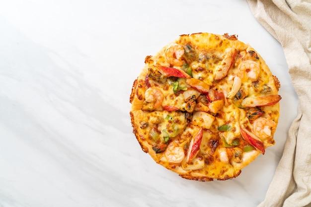 Pizza ai frutti di mare (gamberetti, polpi, cozze e granchi) su vassoio di legno
