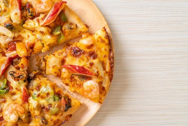 Pizza ai frutti di mare (gamberi, polpi, cozze e granchi) su teglia di legno