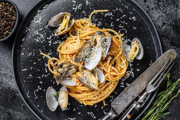 Spaghetti ai frutti di mare con vongole alle vongole in un piatto. sfondo nero. vista dall'alto.