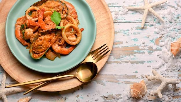 Curry in polvere di frutti di mare in polvere sul piatto in ceramica verde sulla tavola di legno