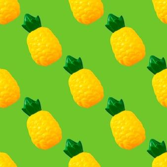 Modello senza cuciture ananas. frutta di plastica del giocattolo isolata su fondo verde. frutta in plastica per selvaggina