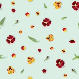 Modello senza cuciture con fiori naturali fiori viola del pensiero boccioli foglie fresche petali su pap verde chiaro