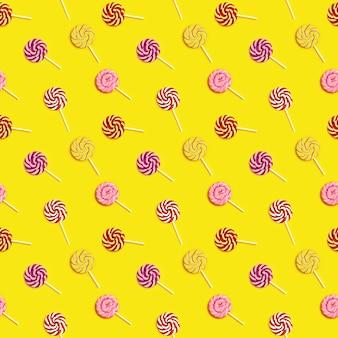 Modello senza cuciture con lecca-lecca caramelle rotonde dolci con strisce su bastone su sfondo di carta gialla.