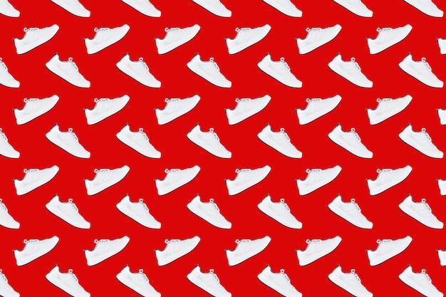 Modello senza cuciture con scarpe da ginnastica bianche su sfondo rosso