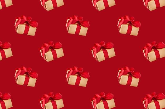 Modello senza cuciture con confezione regalo incartata con nastro festivo su sfondo rosso. concetto di vacanza