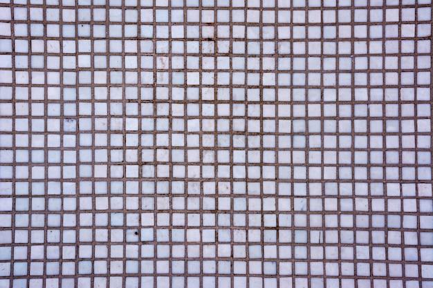 Trama di piastrelle quadrate bianche senza soluzione di continuità. fondo e struttura astratti delle tessere di mosaico bianche.