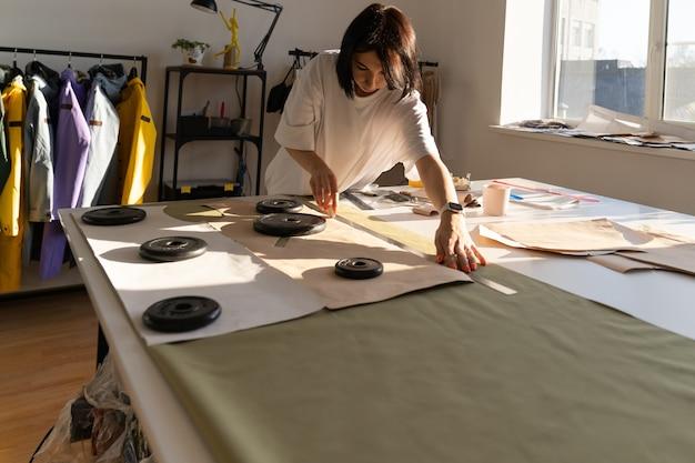 Modelli di carta da bozza di sarta su tessuto con gesso e righello designer di vestiti lavorano in studio